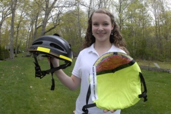 Barrington's Sarah Finnerty holds up a traditional bike helmet, and the one she designed that helped her win the state science fair.