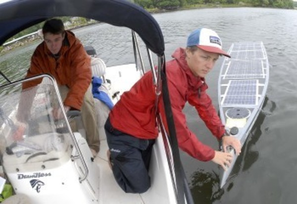 Brendan Prior holds Scout's bow while Dylan Rodriguez steers the chase boat on Nanaquaket Pond during a rainy test run.