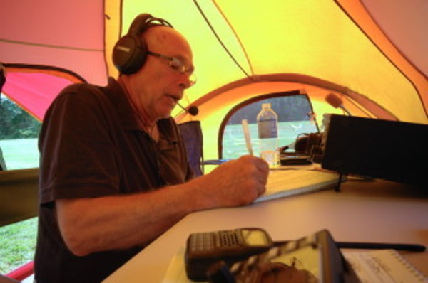 Willy MacLean, president of the Newport County Radio Club, makes contacts under a tent at Glen Park on Saturday. Mr. MacLean was using a shortwave radio being run off a gas-powered generator.