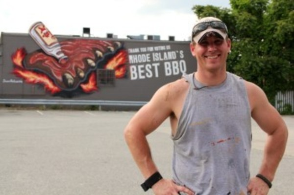 "Paul Leighton with the mural he painted on the side of Rick's Roadhouse in Providence. ""It was my first,"" he said, ""and I'd love to do more."""