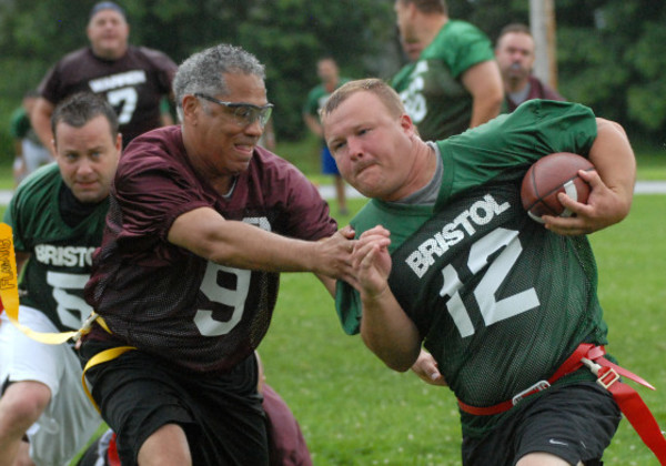 Photos by Rich DionneBristol's Joe Bagwell (right) runs a sweep during the first annual Bristol-Warren Alumni Flag Football Game hosted by the Bristol-Warren Gridiron Club at Kickemuit Middle School on Saturday night.