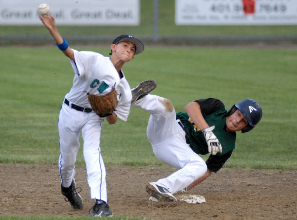 Photos by Rich DionneKing Philip runner Shaun Garrity flips over the second base bag as Cranston Western shortstop Anthony Eucello attempts to complete a double play.