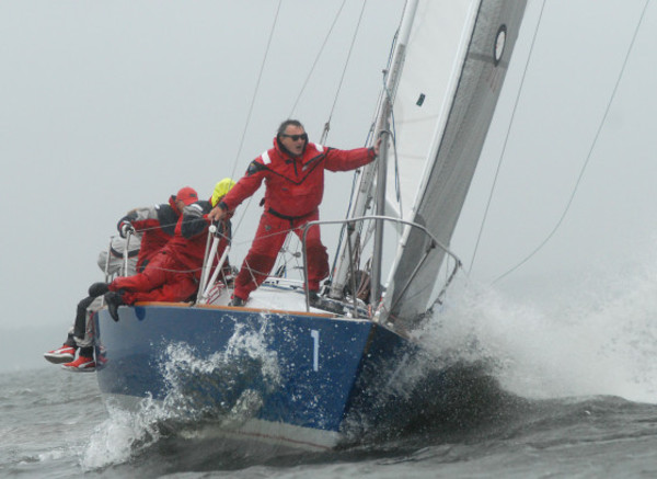 Photos by Rich DionneDon Miller (front) yells back to crew mates as the Falcon approaches a windward mark during a race on Friday.