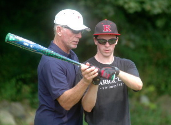 Mike Schmidt helps Colin Martin with his grip during the free clinic Thursday at Portsmouth Abbey. Mr. Schmidt lives at the Newport Beach Club, which is part of the Carnegie Abbey Complex.