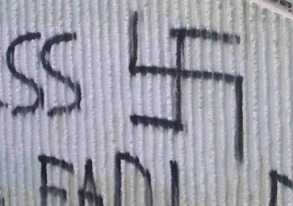Alleged arsonists sprayed swastikas and race-related graffiti while perpetrating the crime four years ago.