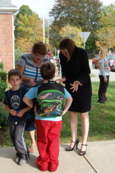 Commissioner Gist talks with Rockwell second-grader Nicholas Docouto, who greets his grandmother Carolina Docouto, and cousin, first-grader Matthew Docouto.