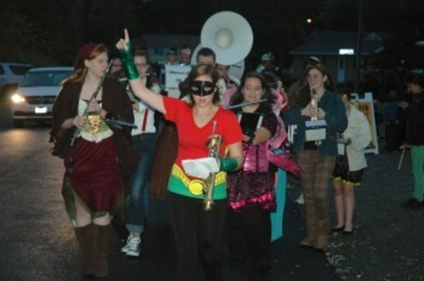 Lauren McKone (center), dressed as Robin, leads the band at the start of the parade.