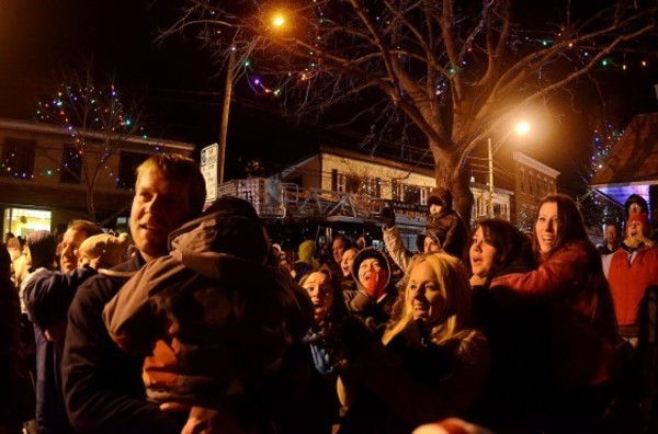 Photos by Rich DionneThe gathering cheers as the lights are turned on in front of town hall during the 25th Warren Holiday Festival on Friday night.