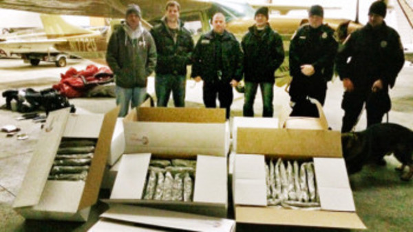 Officials in Pennsylvania display 300 pounds of marijuana from Cessna 207A (rear).