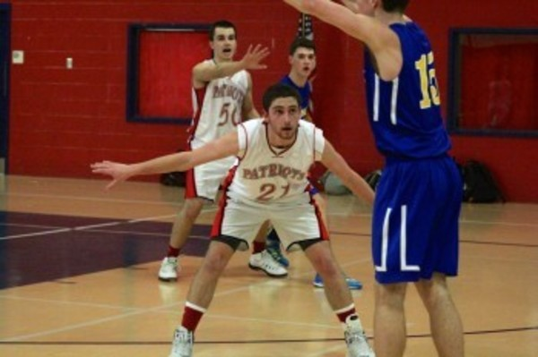 Ryan McVicker defends against a North Providence player. The Patriots' Chris Carpenzano is in the background.