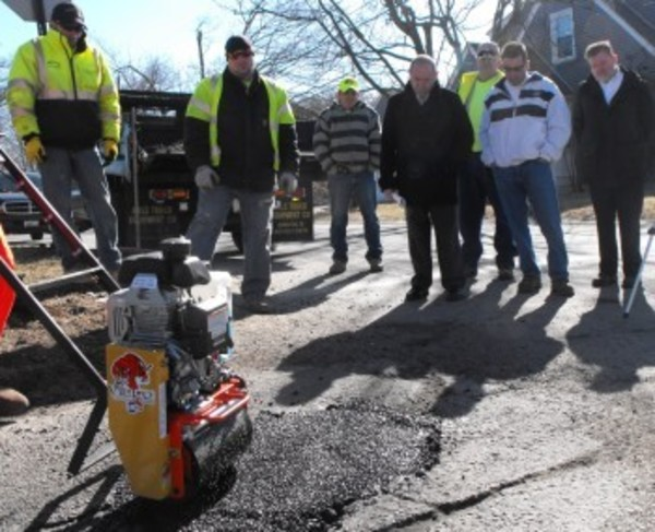 Bristol town officials and DPW crews learn how to use a vibrating roller given to the town in an effort to make RI pothole free.