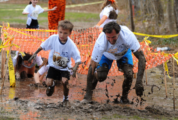 Photos by Rich DionneDylan Edwards, 5, and dad, Scott make their way out of the mud pit during Hamden Meadows School's first ever Tough Tiger event on Saturday.