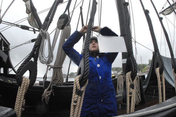 "Photos by Rich DionneCrew person Kaley Soud preps the ""Nina"" for boarding in the pouring rain at the Herreshoff Marine Museum dock on Thursday."