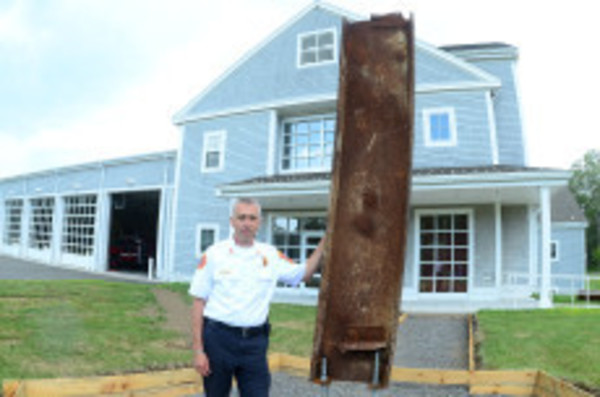 Deputy Fire Chief Allen Manley stand beside the steel beam that was once part of the World Trade Center twin towers. (Tichard W. Dionne photo)
