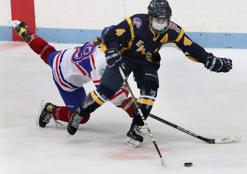 Melissa Levreault skates the puck out of the East Bay zone with a Mounty on her back in the second period during the East Bay girls hockey team's 5-1 victory over Mount St. Charles at Adelard Arena on Tuesday night.