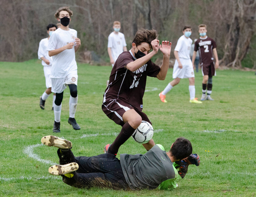 Sophomore forward Owen Couto is tripped up by Old Colony goalkeeper Owen Best in a high speed collision as they vie for the ball.