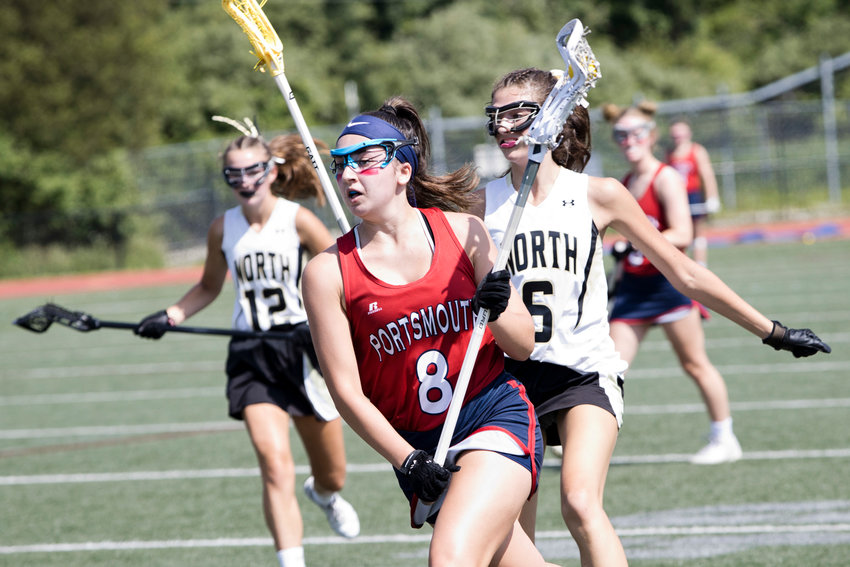 Portsmouth High's Grace Boneu is followed closely by North Kingstown opponents while racing the ball toward the net in the Division II championship game in Cumberland Sunday afternoon.