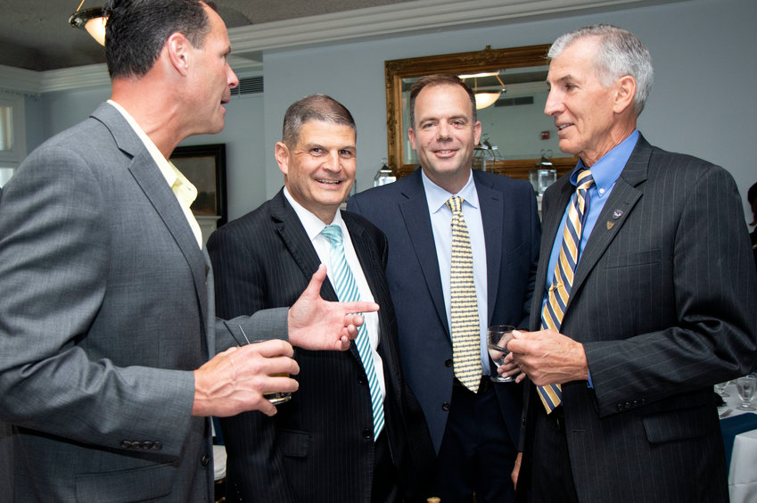 Retiring Barrington Police Chief Dino DeCrescenzo (second from left) smiles while speaking with former police chief John LaCross (right) and current Barrington Police Lt. Kevin Igoe (second from right) during a special retirement party for Chief DeCrescenzo.