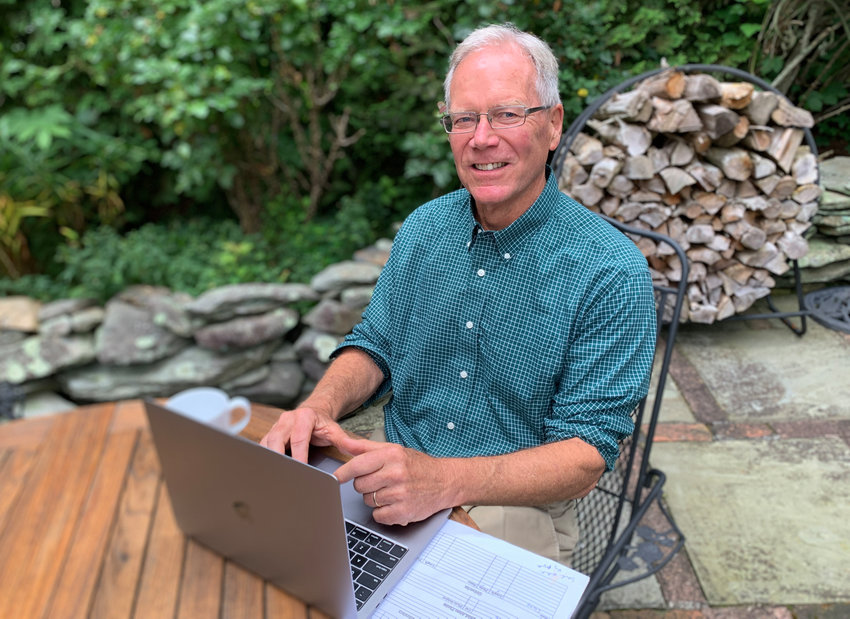 """Bruce Burdett at a patio table outside his Bristol home, where he often works. The editor of The Sakonnet Times and Westport Shorelines is retiring this week after 45 years with East Bay Newspapers. """"There's something in all of us that likes to tell people stories, and this was my way to be able to do it,"""" he said."""