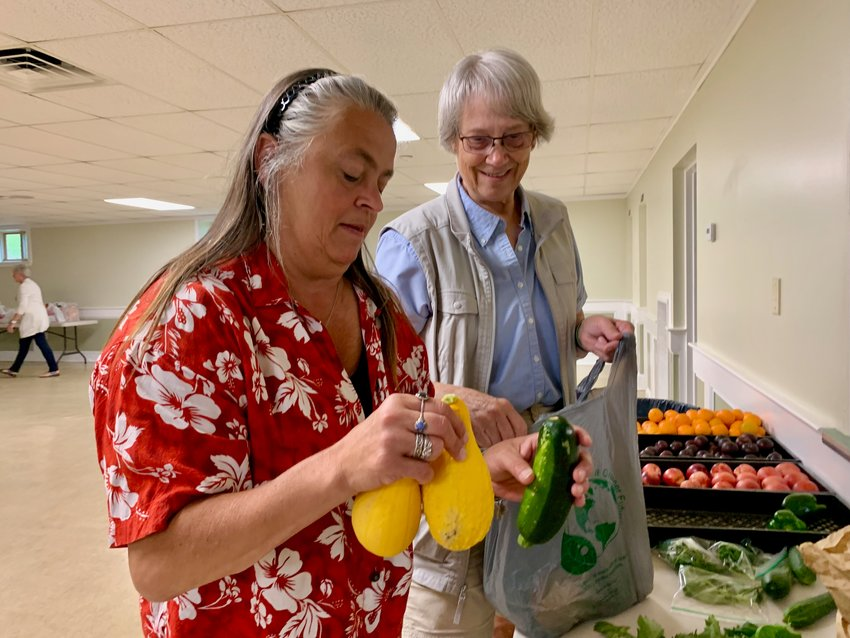 Mary Anne Crittenden (left), director of the St. John Lodge Food Pantry on Sprague Street, along with volunteer Peggy Matteson, bag fresh produce donated by a local resident Wednesday morning. They remind farmers and other residents that the pantry gladly accepts any surplus fresh produce. The food bank feeds about 45 to 50 families every week.