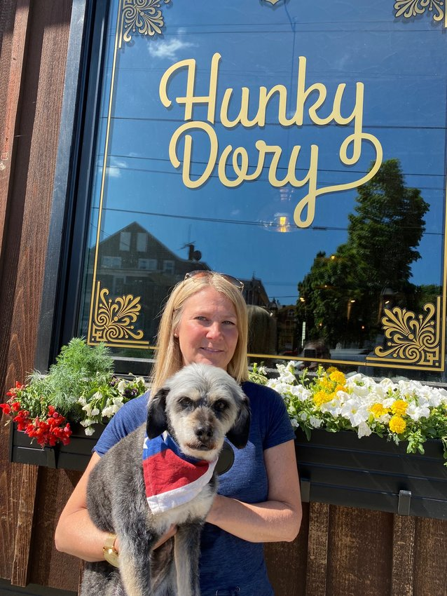 Kerri Payne of Residential Properties, along with her dog Penelope, pose in front of Hunky Dory in downtown Warren, one of the participating businesses of the Dog Stroll.
