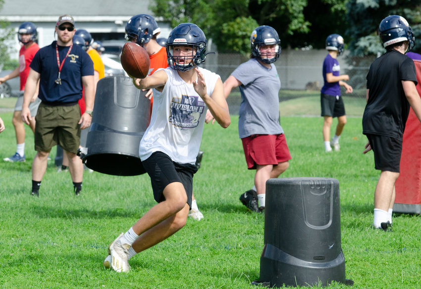 Barrington High School quarterback James Anderson flips the ball to a back during a drill on the first day of preseason football practice on Monday morning, Aug. 23.
