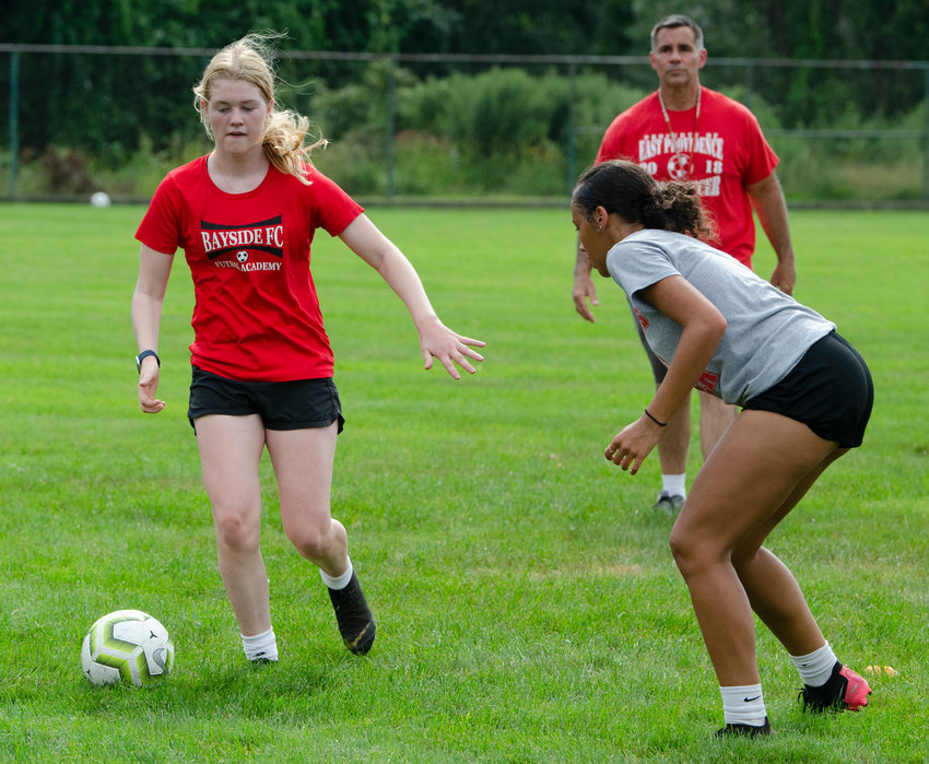 East Providence High School girls' soccer senior captain Lily Budnick (left) dribbles the ball towards classmate and fellow team captain defender Briana Lopes with head coach Angelo Pizzi looking on during a Townies' 2021 preseason practice earlier this week.