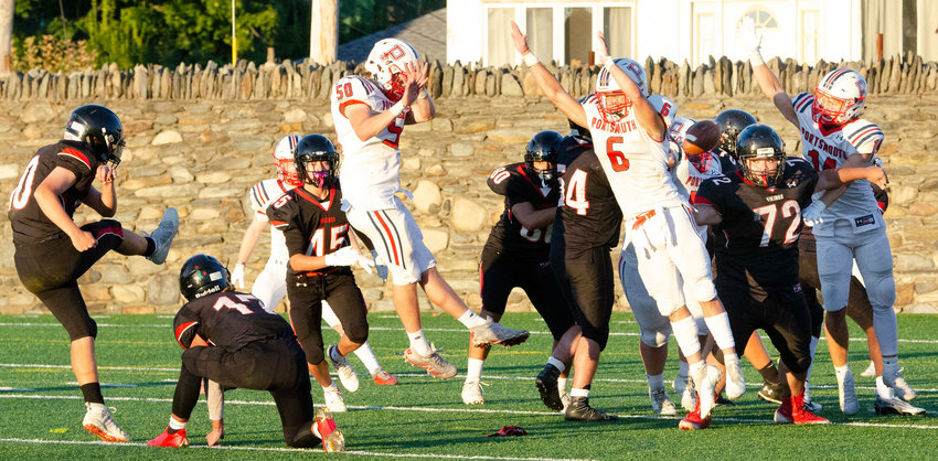 The Patriots' Henry Roderigues (left) Marcus Evans (middle) and others block a Rogers extra-point attempt in the second quarter during Friday night's game.
