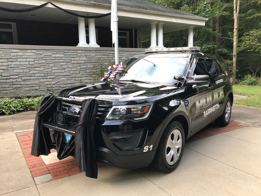 Barrington Police Sgt. Gino Caputo's cruiser is draped in black cloth and flowers rest on the windshield. Sgt. Caputo died on Saturday morning, Sept. 11, after a five-week battle with Covid-19.