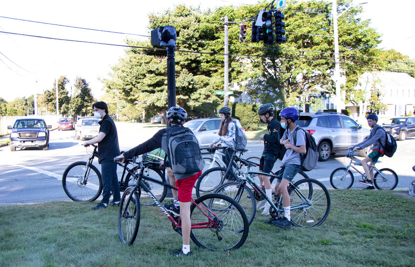 Barrington students wait at the intersection of County Road and Federal Road during the morning commute on Monday. Some parents are concerned about the district's decision to eliminate some bus stops and strictly enforce the two-mile ridership eligibility rule.