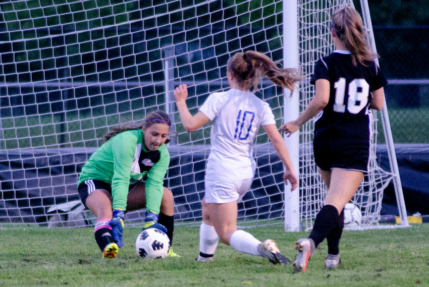Huskies goalkeeper Logan Levesque snatches up the ball, from a Cumberland forward with teammate Sarah Gale (right) during their game against Cumberland on Tuesday night.