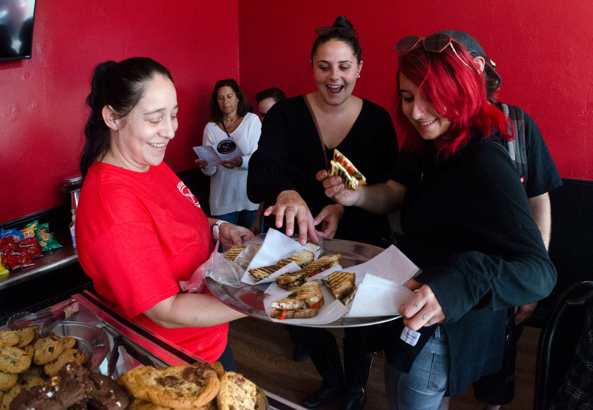 Chef and entrepreneur Courtney Poissant offers panini samples to friends attending the soft opening of her new venture, CP's Catering and Sandwich Shop, last Thursday, Sept. 30. Her menu includes a variety of sandwiches, from classic to creative, that can be had as panini, subs, or wraps.