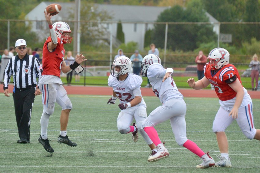 Portsmouth High quarterback Ben Hurd passes over two defenders in the first half of Saturday's Homecoming game against East Greenwich. He had a big day, to say the least.