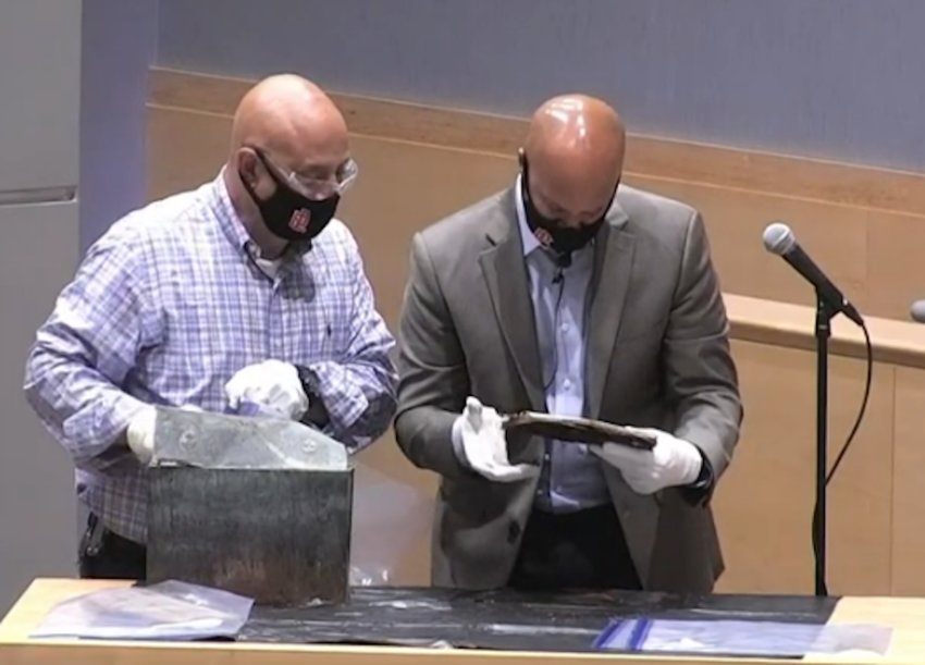 Facilities Director Tony Feola (left) and School Committee chairman Joel Monteiro, during the October 12 meeting of the body, open the time capsule found in the old EPHS building.