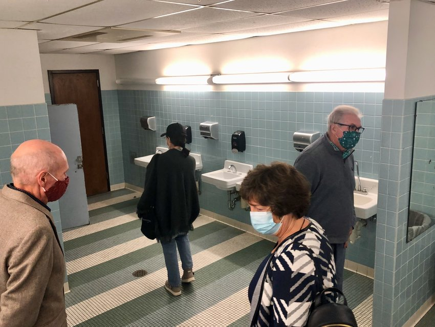 School Committee members (foreground, from left) Thomas Vadney, Emily Copeland and Fred Faerber II inspect the seventh-grade boys' bathroom at Portsmouth Middle School following Monday night's forum on the upcoming school bond. Bathrooms in all four schools would be fully renovated as part of the district's $21.44 million facilities improvement project that goes before voters on Nov. 2.