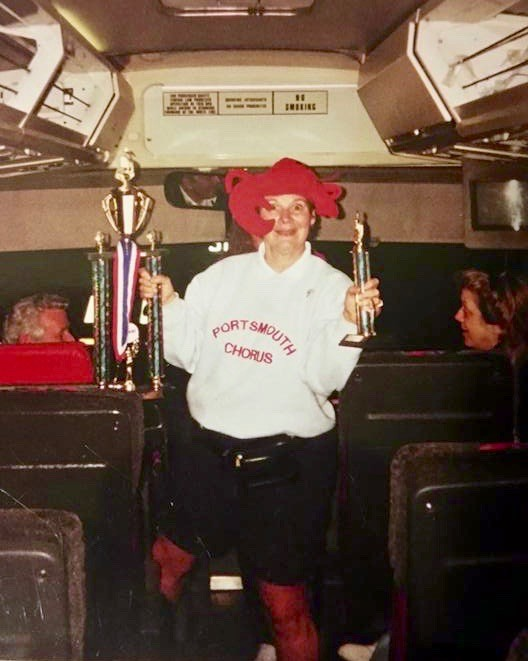 Kate Grana shows off trophies the Portsmouth High School chorus won during a festival at Hershey Park in Pennsylvania in 2002 or 2003. Her sense of humor and joyful personality were among the qualities that endeared her to students. This photo was shared by a former chorus member, Ryan Spero.