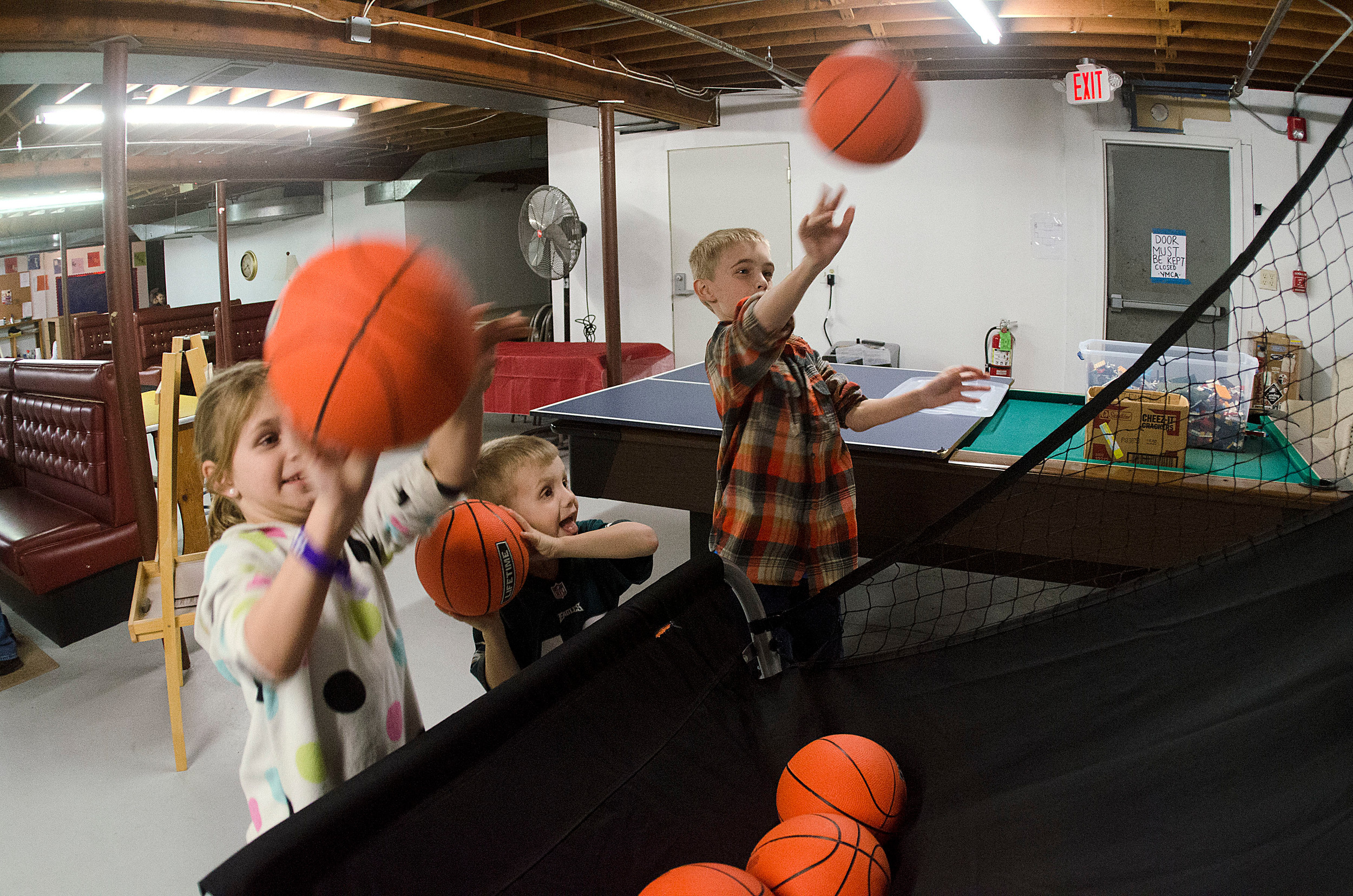 Brooke Marston, 7, Chase Marston, 5 and Jack Marston, 9 (from left), play a basketball shooting game in the basement of the Common Fence Point Community Hall. They were there for the after-school program facilitated by the Newport County YMCA.