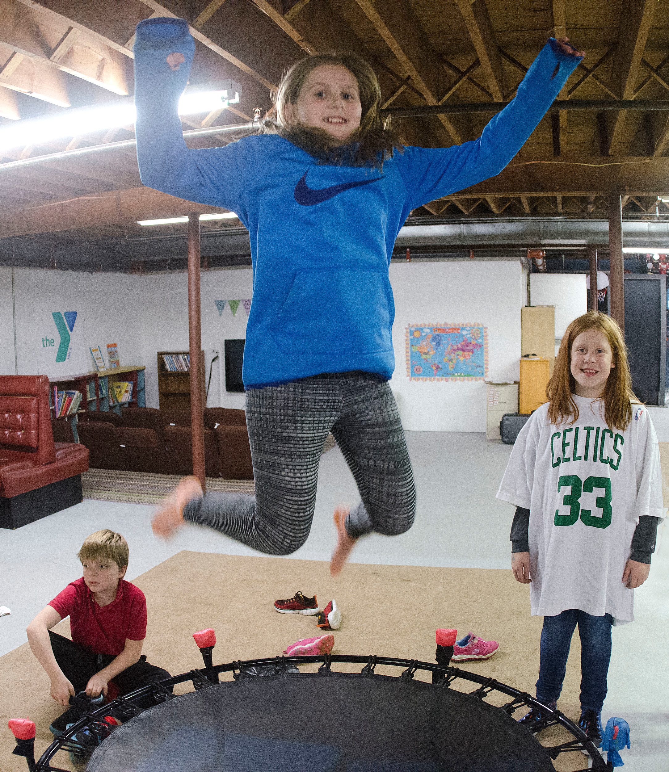 Caitlin Mediate, 10, jumps on the indoor trampoline as her friend, Ava McDermott (right), 9, and another boy look on.