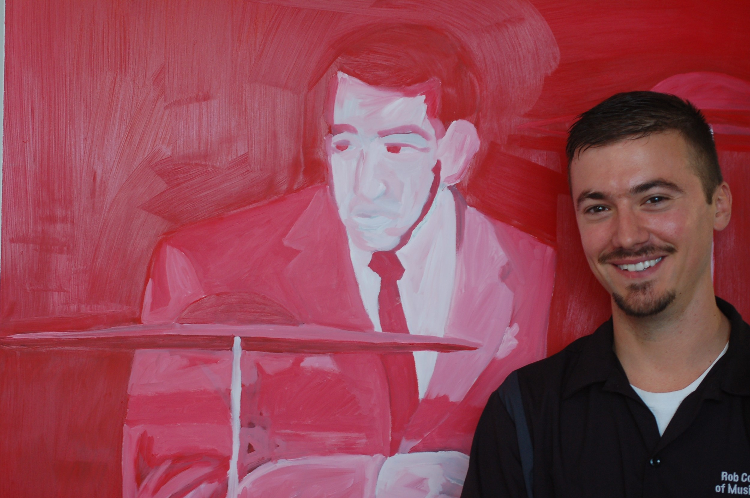 Rob Coyne, of Rob Coyne's School of Music Education, with Matt Charros' painting of legendary Jazz drummer (and Coyne's hero) Buddy Rich.