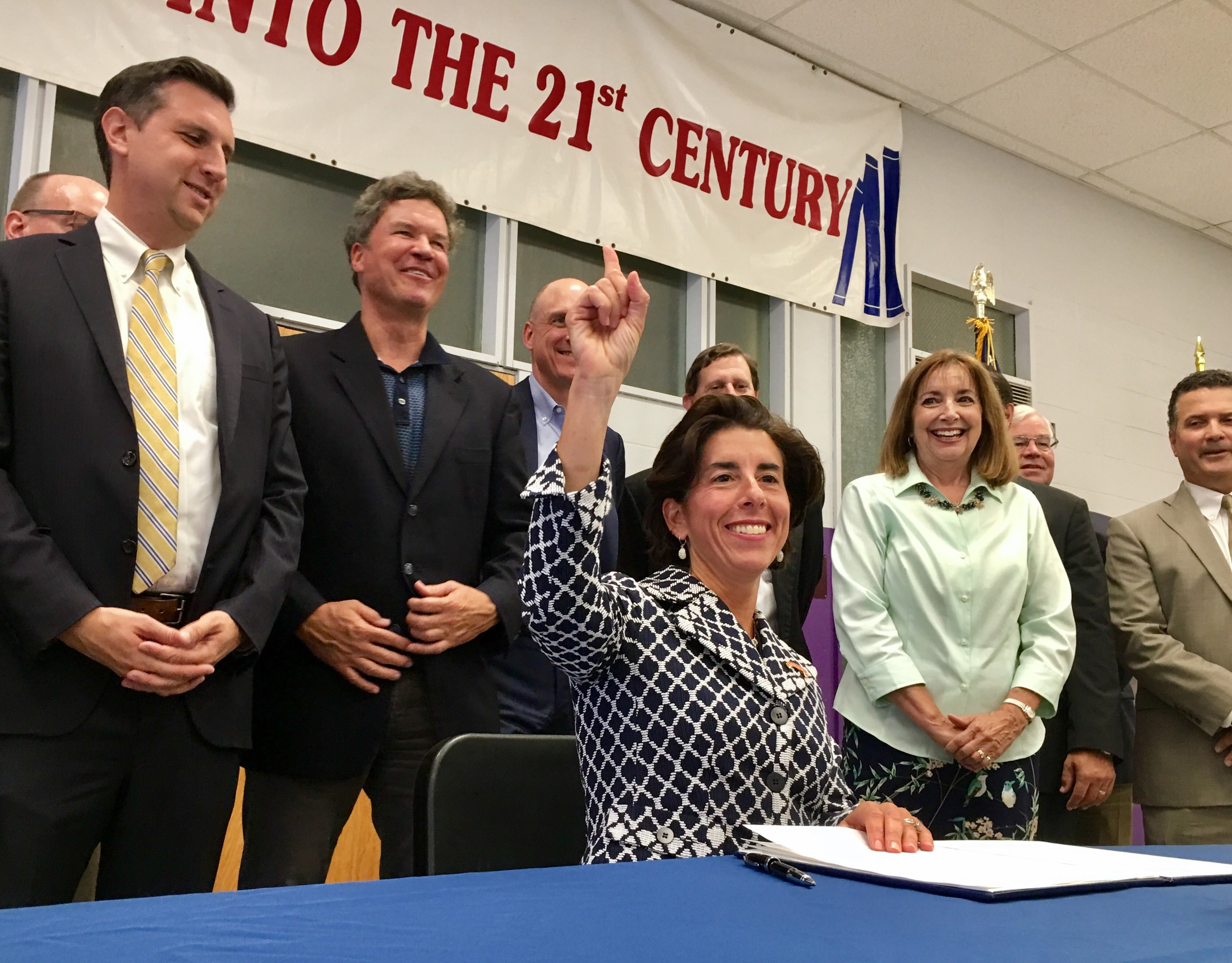 Gov. Gina Raimondo signs paperwork Wednesday creating the Rhode Island School Buildings Task Force, in an event at the Kickemuit Middle School in Warren.