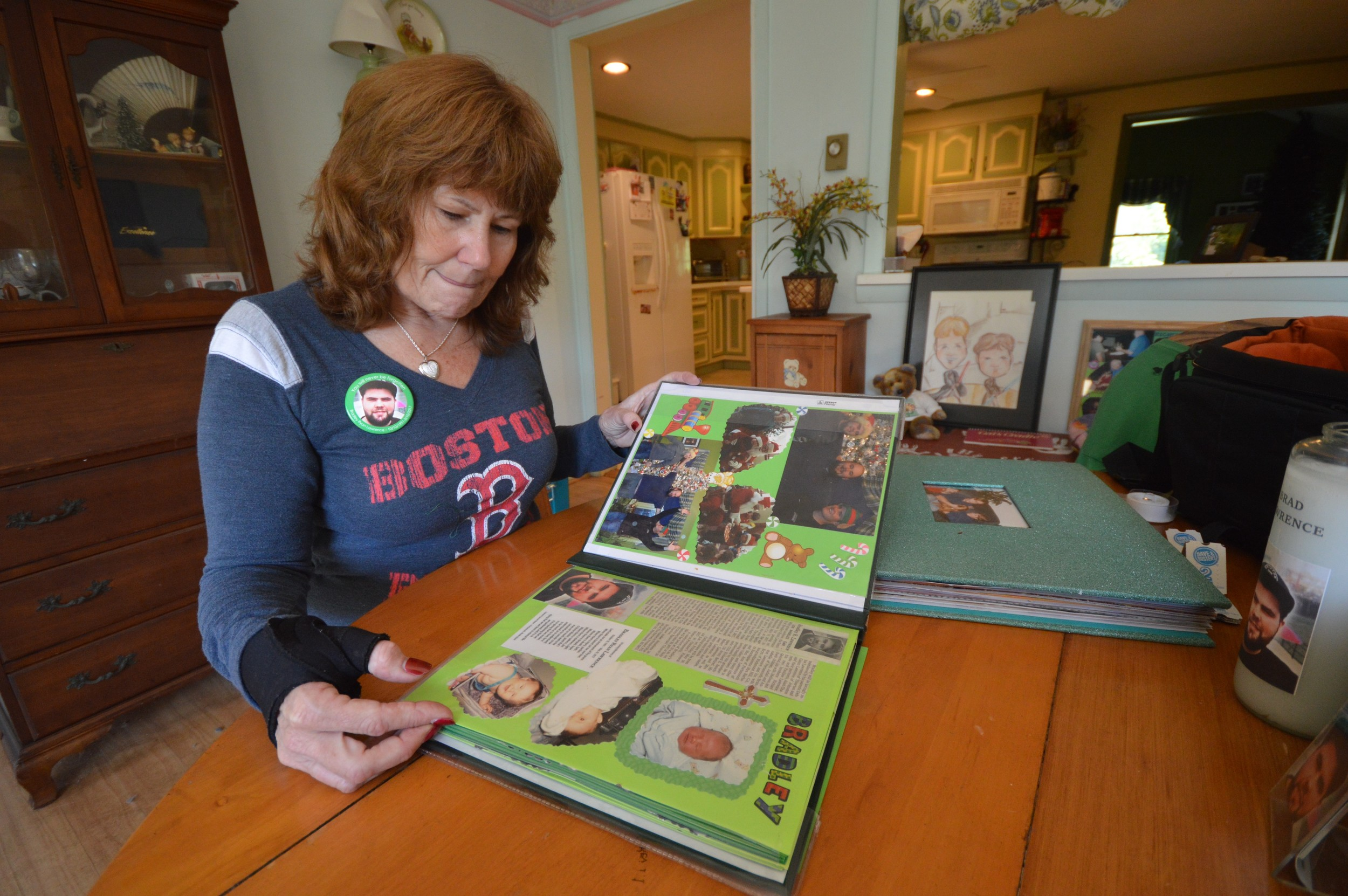"Debbie Lawrence looks over a scrapbook containing photos of her son Bradley, who died May 20 in Los Angeles after suffering from heroin addiction for years. He was 25. ""How many of our kids that Bradley went to school with have died? It's in our backyard,"" she said."
