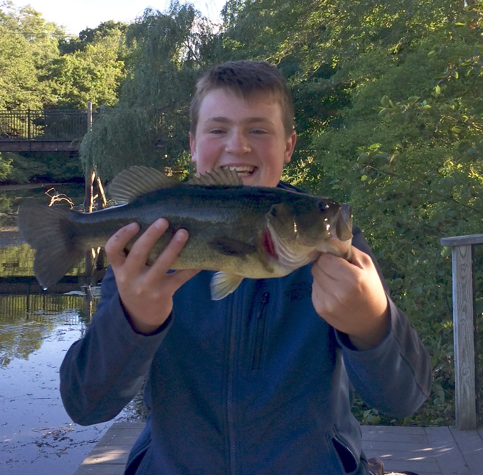Noah Brunelli of Wakefield (13 years old) with the 4.9 pound largemouth bass he caught on the Saugatucket River with worms he dug from the woods next to his home.