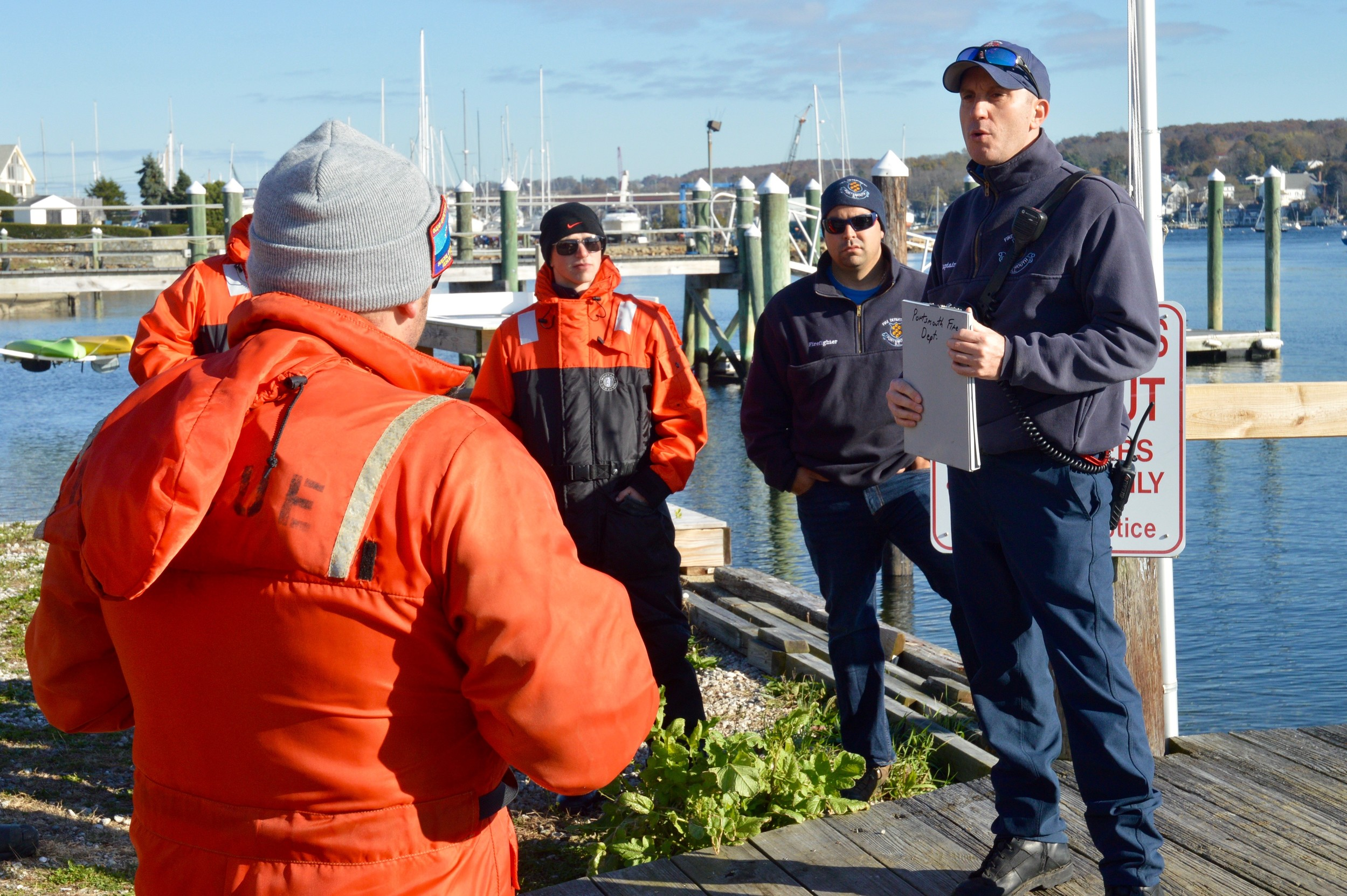 Capt. Steve Lynch (right) of the Portsmouth Fire Department goes over instructions with participants gathered at Stone Bridge Marina before Thursday morning's drill.