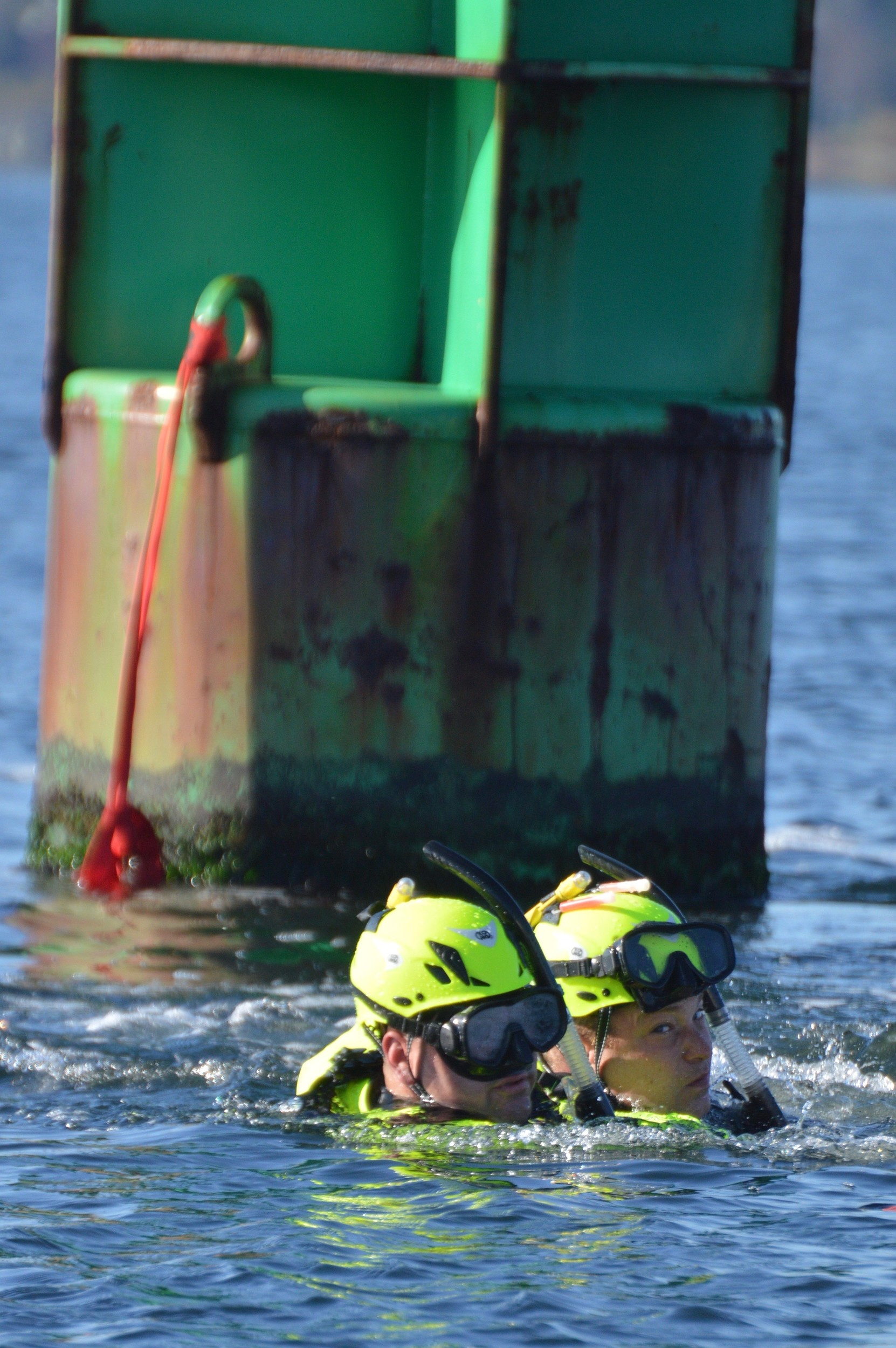 "Portsmouth firefighter Dennis Canario Jr. (left) ""rescues"" Lt. Andrew Jones, playing a swimmer in distress who had been clinging to the green buoy near the opening of the Stone Bridge."