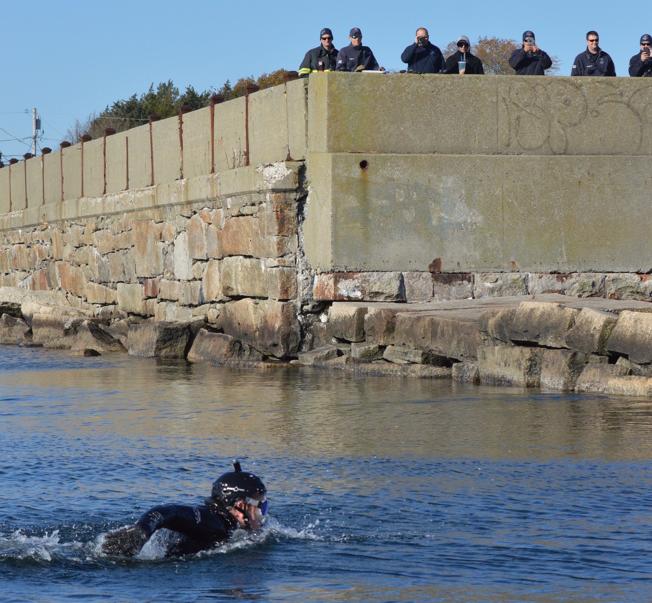 "Firefighter Erik Brierley from the Newport Fire Department swims out to ""rescue"" a swimmer who got caught up on the rocks at the end of the Stone bridge abutment in Portsmouth as other first responders look on above."