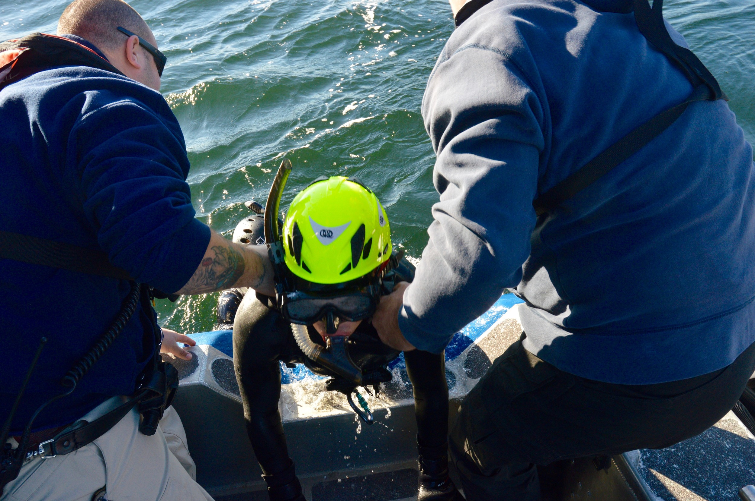 Charlie Dahl of the U.S. Coast Guard, playing a swimmer in distress, is dragged aboard the Portsmouth harbormaster's boat.