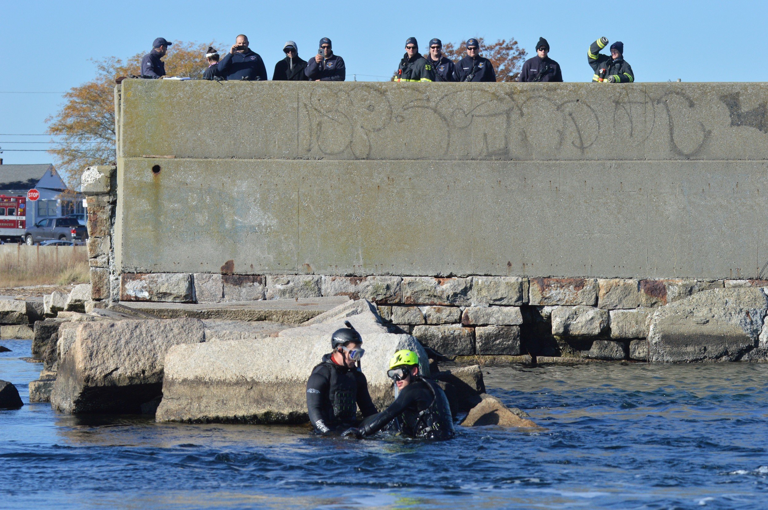 "Firefighter Erik Brierley from the Newport Fire Department (left) is ""rescued"" by Charlie Dahl of the U.S. Coast Guard at the end of the Stone bridge abutment in Portsmouth, as other first responders observe the rescue drill from above."