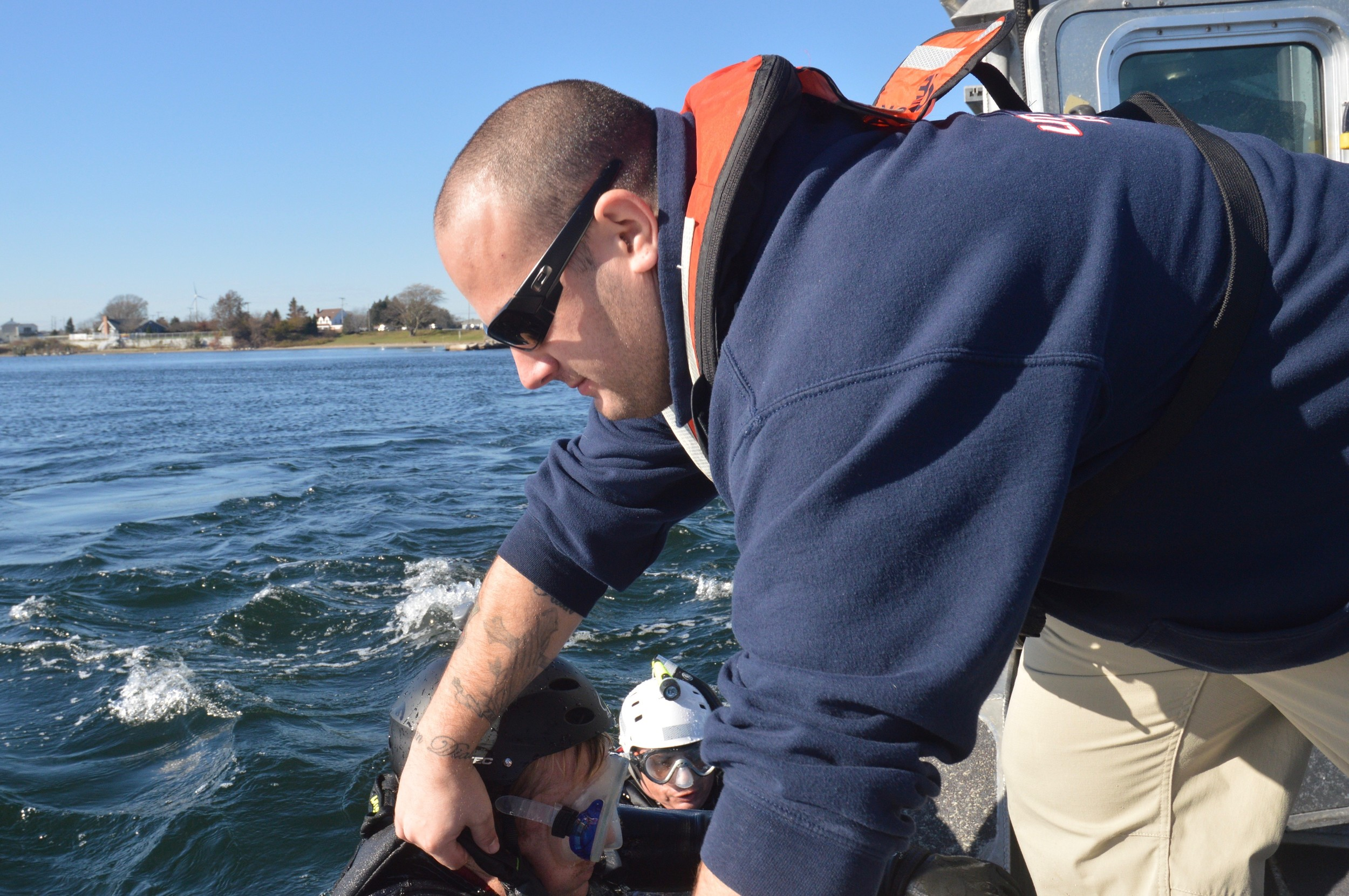 Little Compton firefighter Sam Hussey helps rescue drill swimmers aboard the Portsmouth harbormaster's boat in the Sakonnet River Basin.