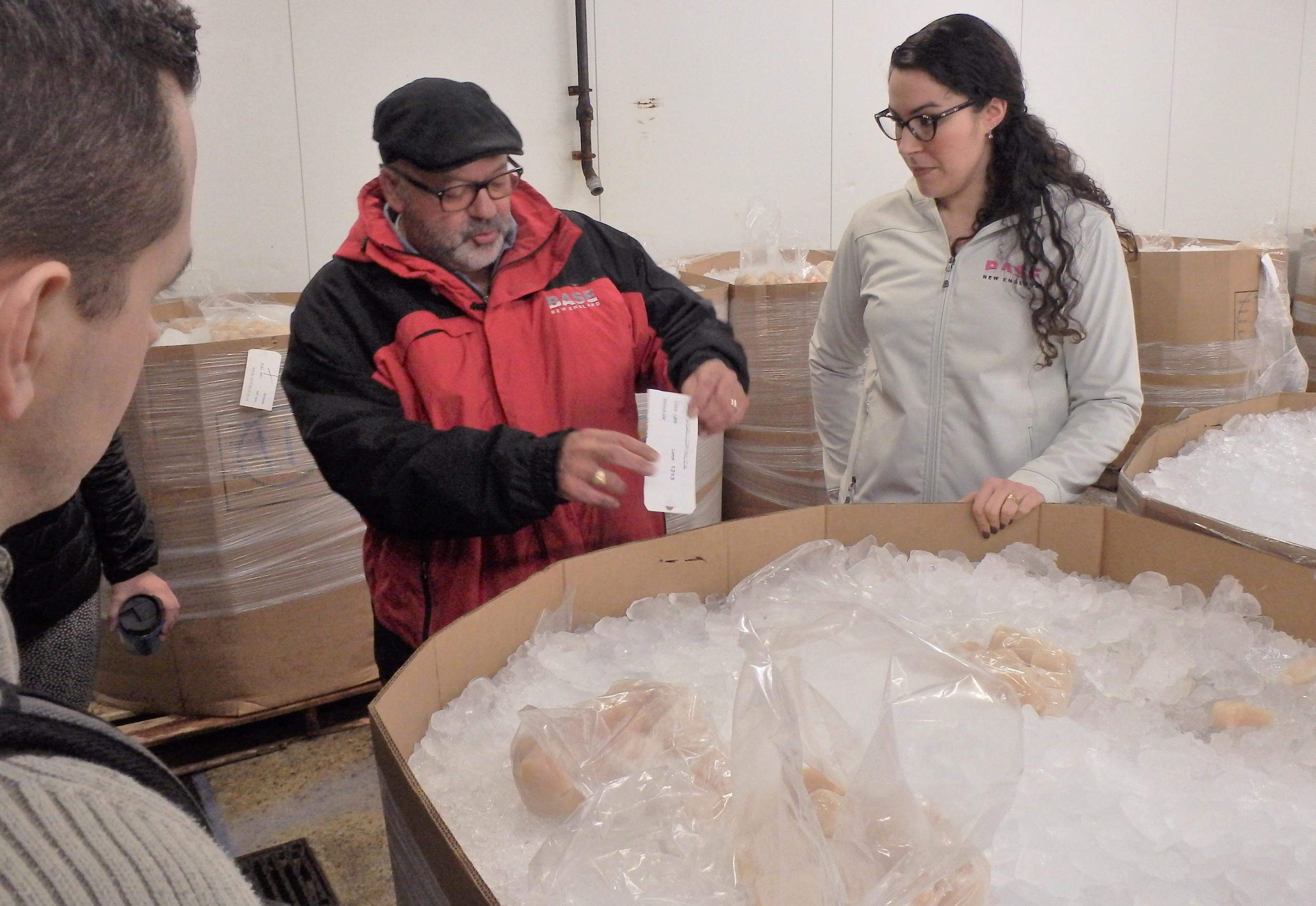 Ritchie Canastra and niece Cassie Canastra of BASE New England in New Bedford, review scallop quality with participants in the Marine Resources Education Program. At $11/pound the bin they are standing over contains about $11,000 worth of sea scallops.