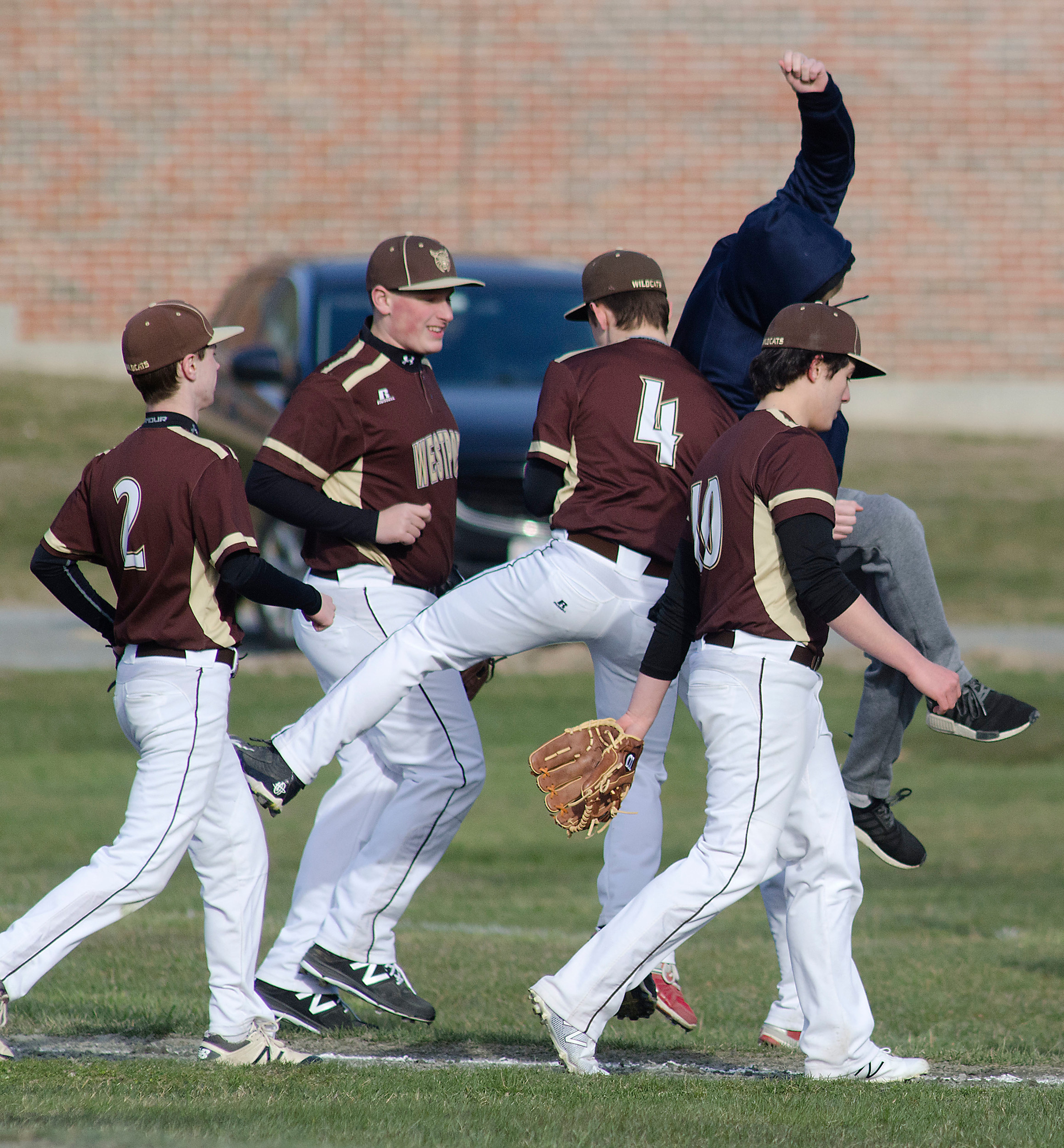 The team celebrates as they run off the field after Dawson Dorvais (4) made a great catch in the outfield to retire the side.